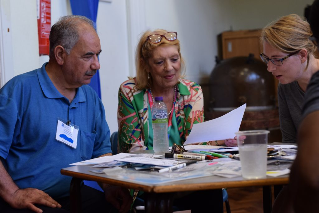 A photo of one of our groups, with  three members looking at a paper resource together and lots of pens on the table.