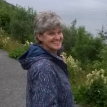 Jane has grey hair and a raincoat- she is standing outside by some plants, overlooking the sea. She is smiling at the camera.