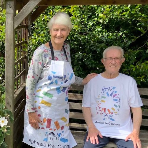 a member wearing his aphasia re-connect t-shirt and his wife in an aphasia re-connect apron. they are outdoors, and the man is sitting on a bench with his wife standing next to him. the apron and the t-shirt are both white, with a colourful circle made up of speech bubbles, and the words aphasia reconnect underneath