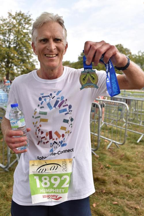 Humphrey holding his half marathon finisher's medal and smiling at the camera, wearing his aphasia reconnect t-shirt